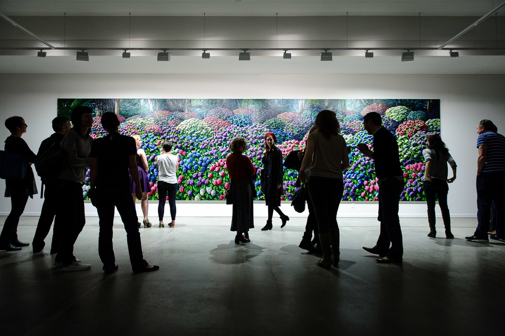 Visitors at the opening of Solo, with Karl Maughan's 'Hydrangeas, Wellington Botantical Gardens', 2014. Photograph: Mark Tantrum